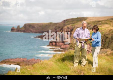 Couple reading map, Chemin de la côte près de Marloes, Pembrokeshire Coast National Park, Pays de Galles, Royaume Banque D'Images