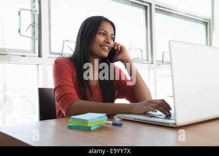 Femme sur l'aide de l'ordinateur portable à la maison Banque D'Images
