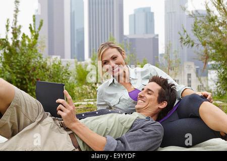 Couple relaxing in park par ville Banque D'Images
