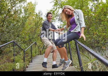 Couple en glissant sur l'étape courante en forêt Banque D'Images