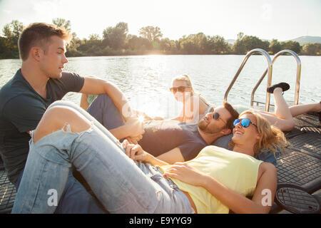 Quatre jeunes amis adultes chatter sur Riverside pier Banque D'Images