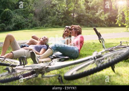 Trois mature woman relaxing on grass après balade à vélo Banque D'Images