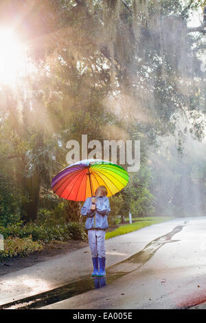 Boy carrying parapluie et looking up on street Banque D'Images