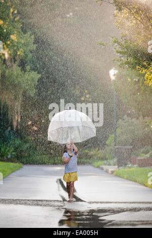 Barefoot girl holding up parapluie et marcher dans des flaques sur la rue Banque D'Images