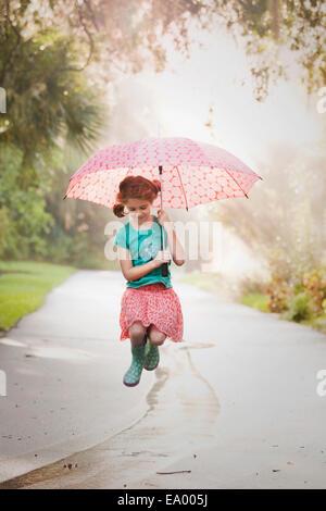 Girl holding up parapluie et sautant de flaques sur street Banque D'Images