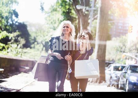 Jeune femme et son mentor shopping et rire sur street, New York City, USA Banque D'Images