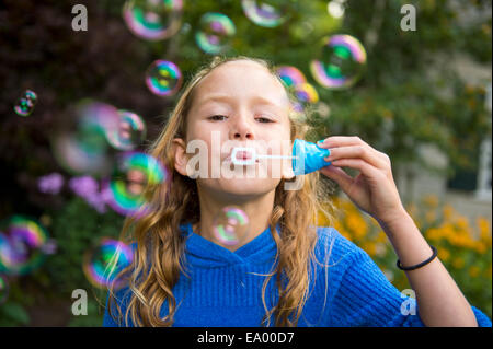 Girl blowing bubbles in garden Banque D'Images