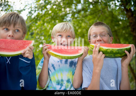Friends eating watermelon in garden Banque D'Images