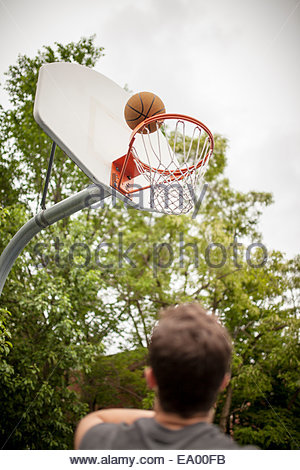 Jeune homme but de basket-ball de notation Banque D'Images
