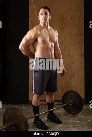 Portrait of mid adult male musculaire avec l'haltérophile barbell in gym Banque D'Images