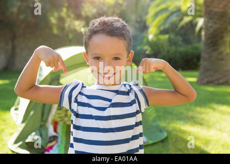 Portrait of boy in garden flexing muscles Banque D'Images