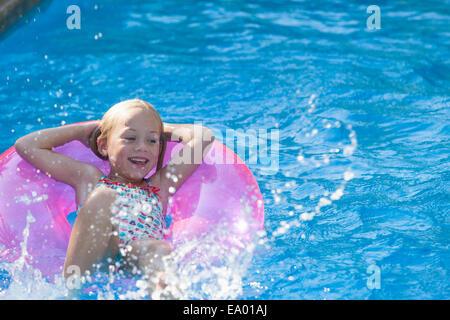 Jeune fille allongée sur le dos sur l'anneau gonflable dans jardin piscine Banque D'Images