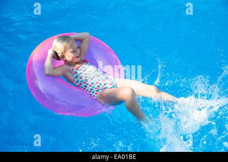 Girl sur anneau gonflable dans jardin piscine Banque D'Images