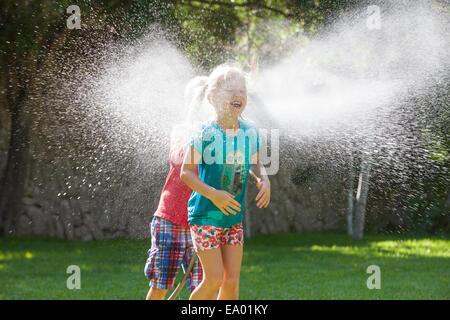 Garçon Fille chassant dans jardin avec arrosage de l'eau