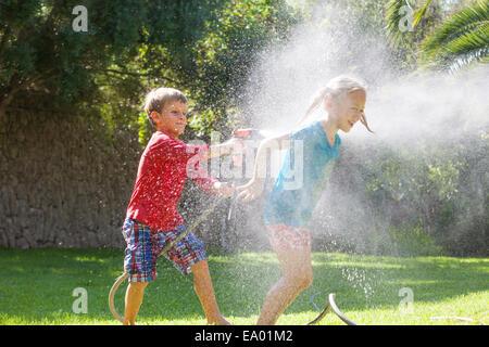 Garçon Fille éclaboussures dans jardin avec water sprinkler