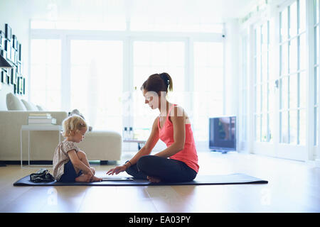 Mid adult mother and toddler daughter practicing yoga in living room Banque D'Images