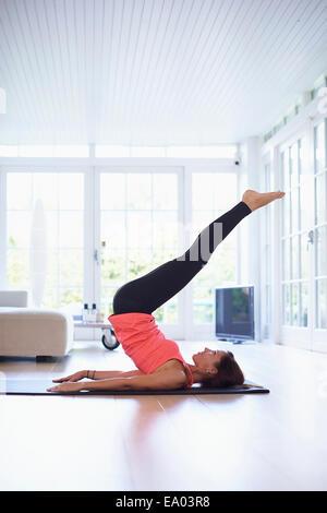 Mid adult woman lying on retour la pratique du yoga dans la salle de séjour Banque D'Images