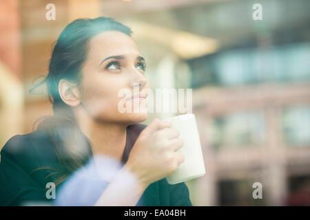 Portrait de boire du café et à la fenêtre de cafe, London, UK Banque D'Images