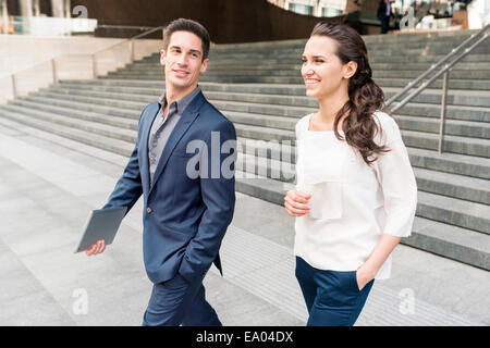 Young businessman and woman chatting en marchant, London, UK Banque D'Images