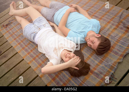 Young smiling couple lying on blanket on jetty Banque D'Images