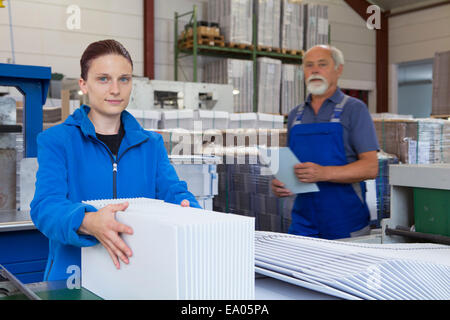 Les travailleurs en usine avec un carton de travail Banque D'Images