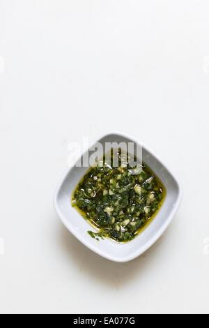 La sauce pesto dans un bol sur fond blanc simple Banque D'Images