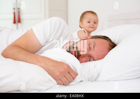 Père endormi dans son lit, regardant sa fille de bébé Banque D'Images
