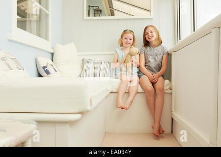 Portrait de deux soeurs assis dans maison de vacances porche Banque D'Images