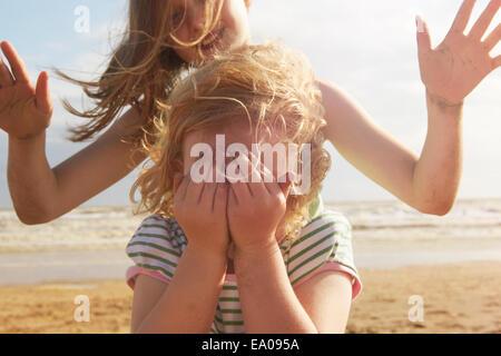 Girl couvrant les yeux en face de soeur sur plage, Camber Sands, Kent, UK Banque D'Images