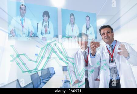 Les médecins spécialistes discuter des résultats par vidéo conférence sur l'affichage futuriste Banque D'Images