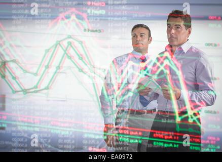 Hommes d'inspection sur l'affichage graphique futuriste interactive Banque D'Images