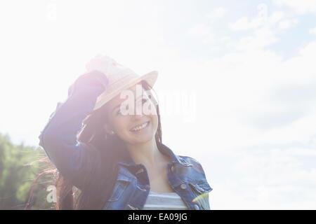 Young woman smiling, la maintenant sur hat