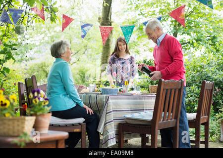 Famille s'asseoir pour un repas en plein air Banque D'Images