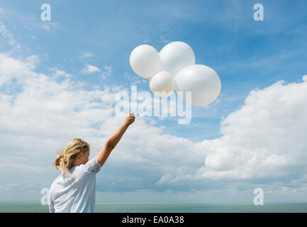 Girl holding white balloons outdoors Banque D'Images