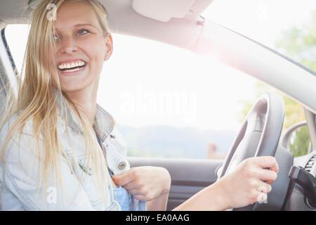 Young woman smiling derrière la roue de voiture Banque D'Images