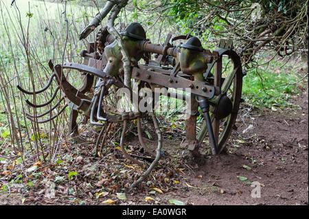 Un vieux hay turner (haybob) abandonné dans une couverture ferme Banque D'Images