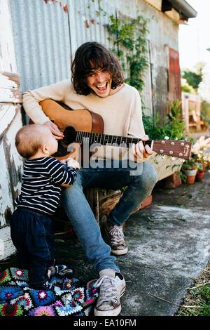 Père Fils divertissant avec guitare Banque D'Images