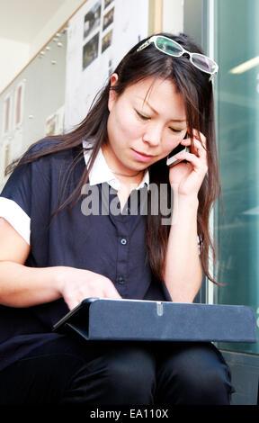 À l'aide d'architecte femelle smartphone et tablette numérique sur l'étape de bureau Banque D'Images