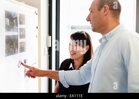 Homme et femme architects looking at blueprints on office wall Banque D'Images