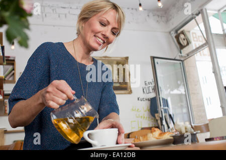 Mid adult woman pouring tea in cafe Banque D'Images