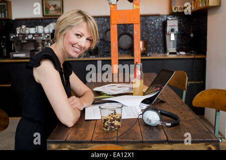 Mid adult woman in cafe with paperwork Banque D'Images