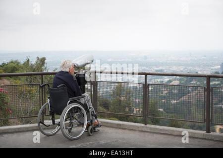 Senior man in wheelchair à la ville à monnayeur par les jumelles de l'affichage de l'Observatoire Griffith Park Banque D'Images