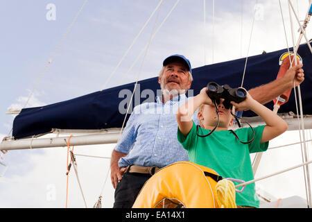 Garçon et grand-père le voilier binoculars Banque D'Images