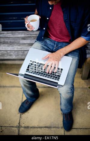 Man using laptop on bench