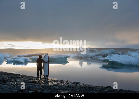 Woman with surfboard, Glacier Jökulsárlón Lagoon, le parc national de Skaftafell, l'Islande Banque D'Images