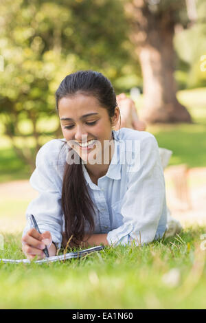 Smiling woman with book and pen in park Banque D'Images