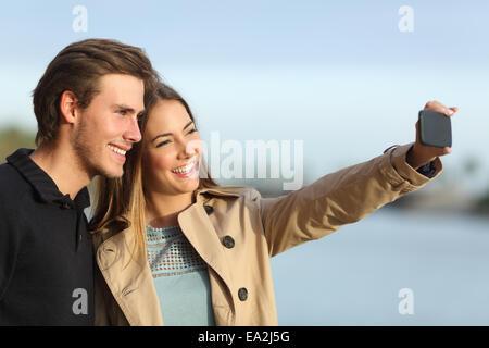 Photographier un couple heureux avec les selfies smart phone outdoors in winter Banque D'Images