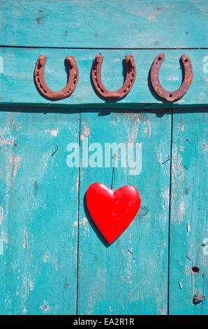 Trois vieux fer à cheval rouillé symbole de chance et de cœur rouge sur la porte Banque D'Images