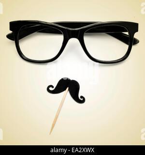 Les lunettes et la moustache représentant un gentleman ou un gars hippie sur un fond beige, avec un effet rétro Banque D'Images