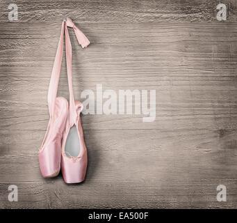 Nouvelles chaussures de ballet rose accroché sur fond de bois.Vintage style. Banque D'Images